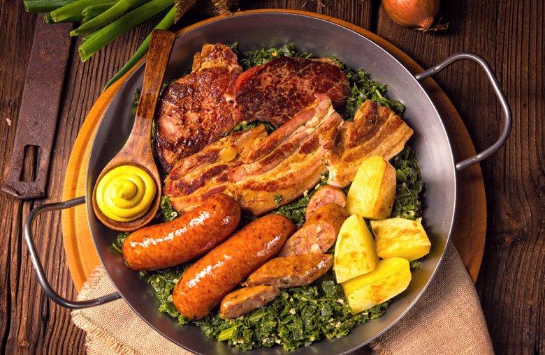 In der norddeutschen Küche wird Grünkohl mit Pinkel, Kochwurst, Kassler, Bauchspeck und Kartoffeln serviert.