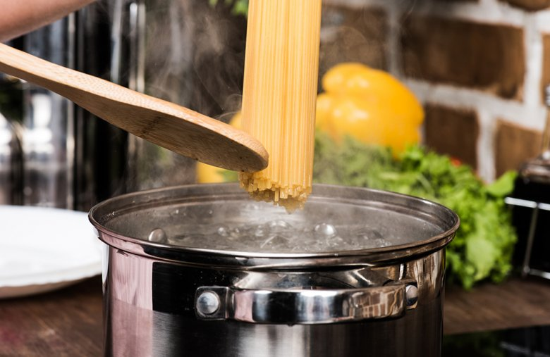 Lebensmittel wie Nudeln werden vorsichtig in die bereits kochende Flüssigkeit gegeben und darin gegart.