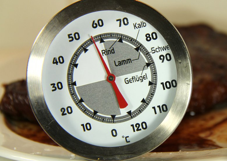 Ein Fleischthermometer hilft dabei zu bestimmen, ob das Fleisch des Spanferkels schon gar ist.