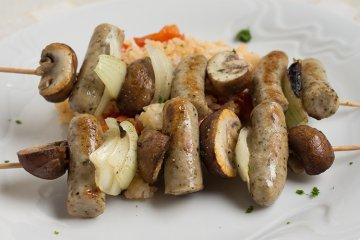 Bratwurst-Spieße auf Tomatenreis mit Champignons