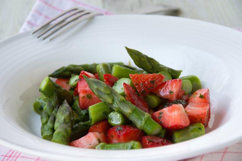 Erdbeeren auf grünem Spargel